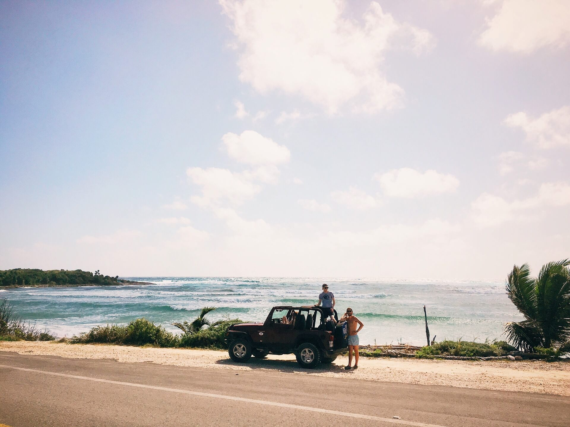 Two man standing next to a car parked on the road close to the beach