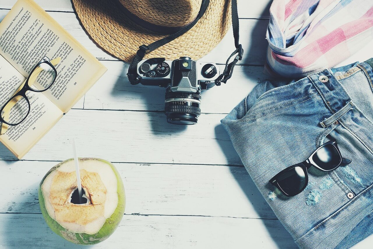 Jeans hat shades a camera and a coconut